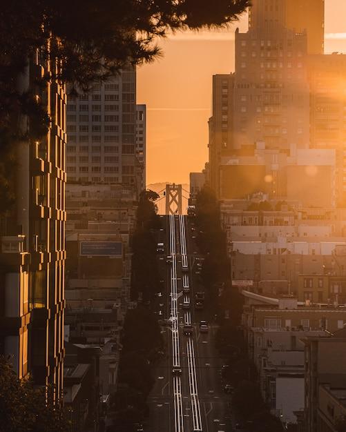 Вертикальный снимок дороги в гору посреди зданий с едущими автомобилями Бесплатные Фотографии
