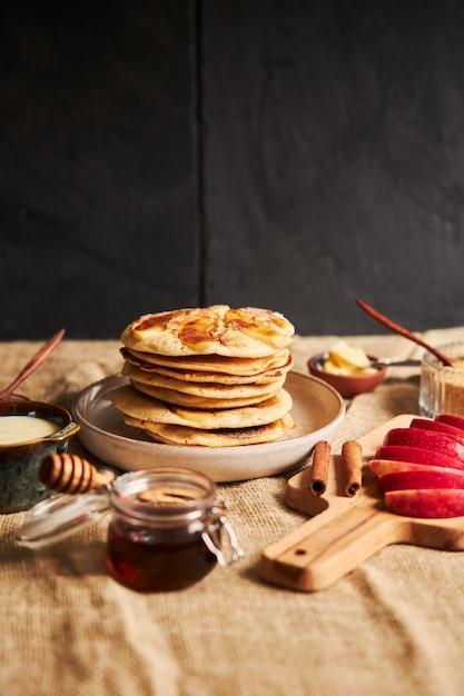 リンゴのスライス蜂蜜と材料を側面に置いたプレート上のリンゴのパンケーキの垂直ショット 無料写真