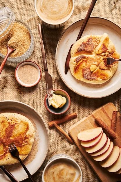 テーブルの上のコーヒーリンゴと他の食材とリンゴのパンケーキの垂直ショット 無料写真