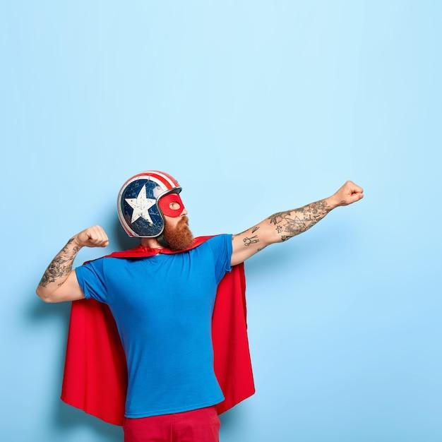 Вертикальный снимок бородатого мужчины делает жест полета, сжимает кулаки, имеет цель достичь Бесплатные Фотографии