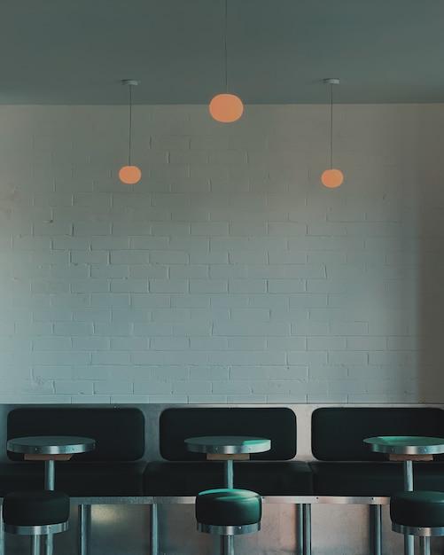 카페에서 받침대 테이블과 벤치 옆에 검은 변의 세로 샷 무료 사진