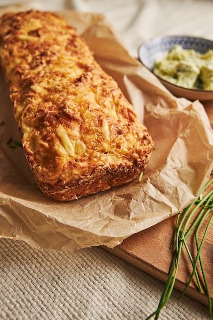 木の上にチーズハーブバターとパンの垂直ショット 無料写真