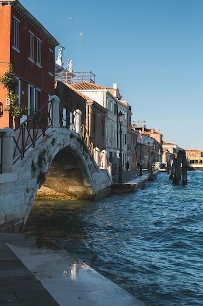 建物とイタリアのヴェネツィアの運河の水に架かる橋の垂直ショット 無料写真