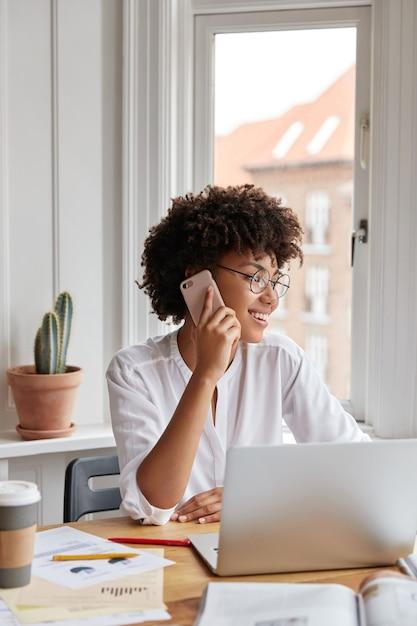 陽気な女性の簿記係が携帯電話で話し、前向きな表現を持ち、ラップトップコンピューターで動作する垂直ショット 無料写真