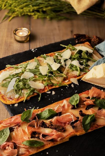 나무 테이블에 베이컨, 야채, 치즈로 가득 맛있는 빵의 세로 샷 무료 사진