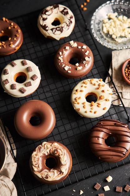 Вертикальный снимок восхитительных пончиков, покрытых бело-коричневой шоколадной глазурью на черном столе Бесплатные Фотографии