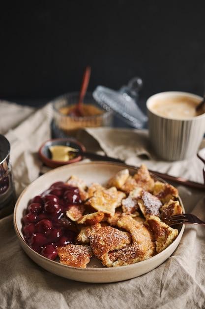 さくらんぼと粉砂糖を使ったふわふわのおいしいパンケーキの縦のショット 無料写真