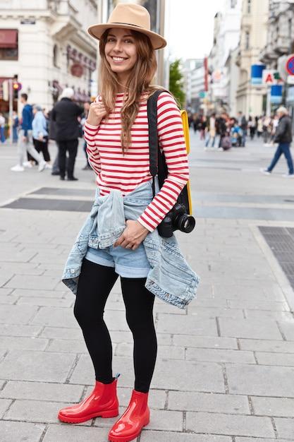 ファッショナブルな女性の放浪者の垂直ショットは、通りを外を散歩し、ファッショナブルな帽子、ストライプのジャンパーを身に着けています 無料写真