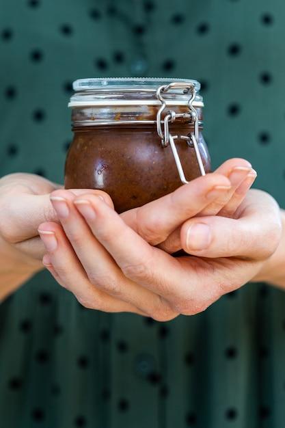 ガラスの瓶に自家製ビーガン生梅ジャムを保持している女性の手の垂直ショット 無料写真