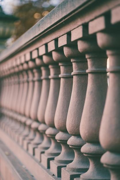 흐릿한 배경으로 햇빛 아래 다리의 울타리 열의 세로 샷 무료 사진
