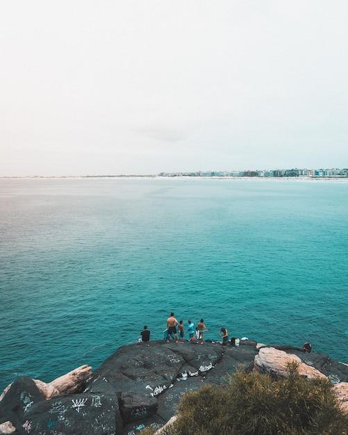 リオデジャネイロの青い海で釣りをしている漁師の垂直ショット 無料写真