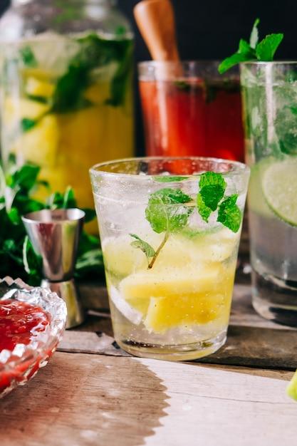 Вертикальный снимок свежеприготовленных холодных напитков с фруктами и мятой на столе Бесплатные Фотографии