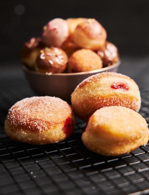 黒いテーブルの上に砂糖とクリームで揚げたドーナツの垂直ショット 無料写真