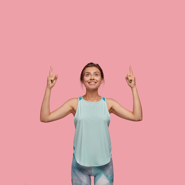Вертикальный снимок радостной европейской женщины с радостью улыбается Бесплатные Фотографии