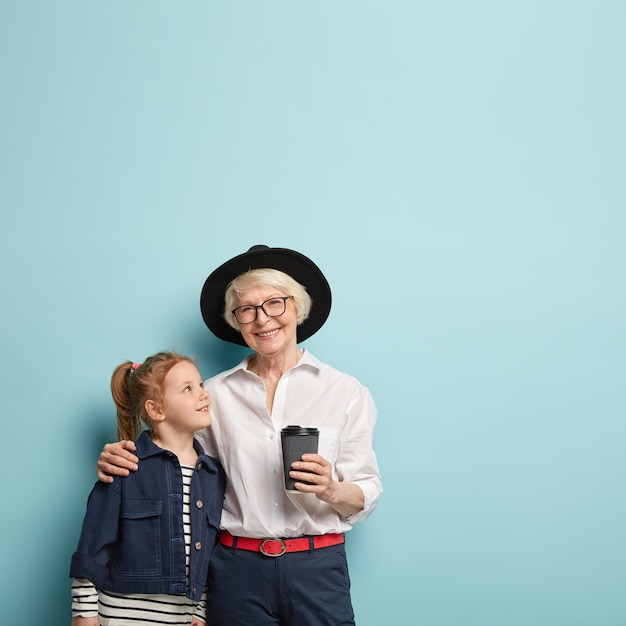 Вертикальный снимок радостной пожилой женщины обнимает свою маленькую внучку, дает несколько советов, носить модную одежду Бесплатные Фотографии