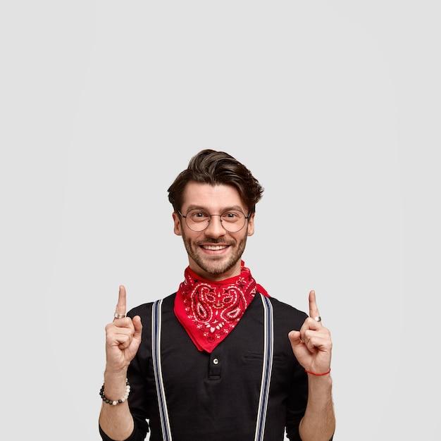 幸せな表情の幸せなひげを生やした男性の垂直ショットは上向き、赤いバンダナと黒いシャツを着て、フレンドリーな笑顔、流行のヘアカット、上のコピースペースで白い壁に隔離 無料写真