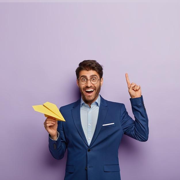 Вертикальный снимок счастливого мужчины-директора в элегантном официальном костюме, показывает указательный палец вверху Бесплатные Фотографии