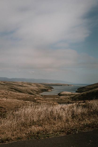 Вертикальный снимок холмов и травы водоем под облачным небом Бесплатные Фотографии