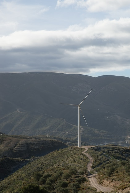 Вертикальный снимок холмов, покрытых зеленью, с ветряной мельницей на фоне под пасмурным небом Бесплатные Фотографии