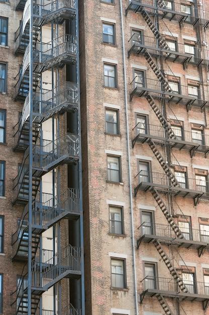 側面に消防階段がある古い石造りのアパートの建物の垂直方向のショット 無料写真