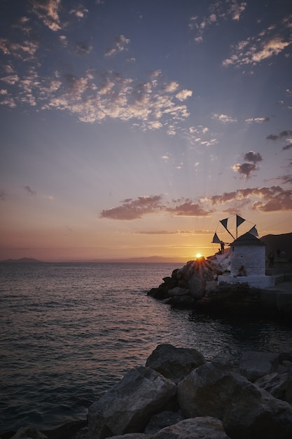 日没時のギリシャ、アモルゴス島のormosegialis風車の垂直ショット 無料写真
