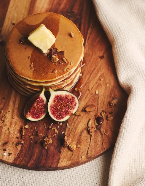シロップ、バター、イチジク、木の板にローストナッツのパンケーキの垂直ショット 無料写真