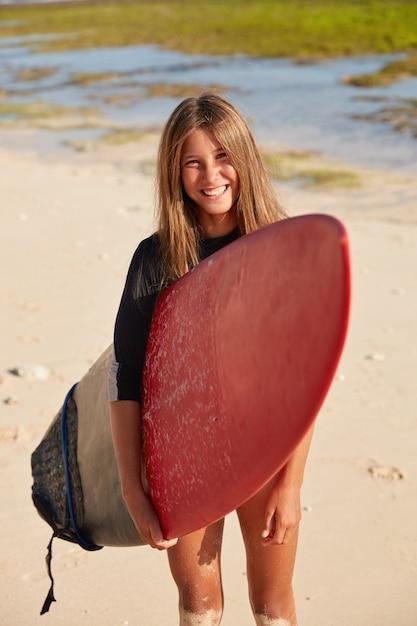 サーフィンの準備ができて、赤いサーフボードを運び、熱帯のビーチで自由な時間を過ごす、快適に見えるアクティブなサーファーの垂直ショット 無料写真