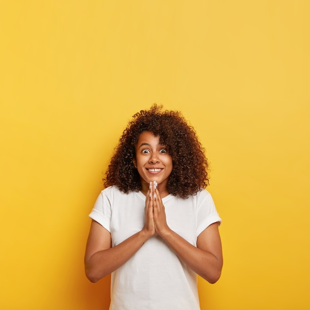 かなり縮れた髪の10代の少女の垂直ショットは、幸せそうな表情を驚かせ、広く笑顔で、祈りのジェスチャーで手のひらを一緒に保ち、神の助けを信じ、希望に満ちた表現をし、白い服を着ています 無料写真