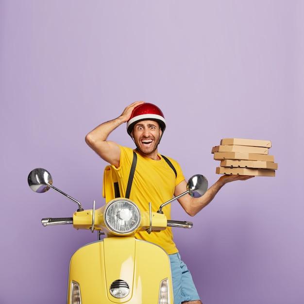 ピザの箱を持って黄色いスクーターを運転する怖い配達員の垂直ショット 無料写真