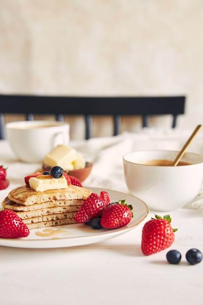 フルーツとシロップを添えたスライスしたビーガンパンケーキの垂直ショット 無料写真