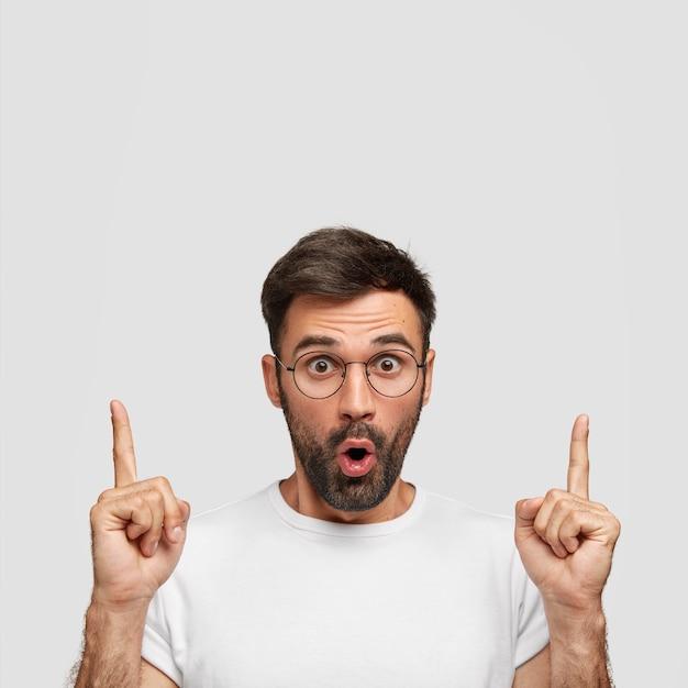 Вертикальный снимок ошеломленного бородатого молодого человека с испуганным выражением лица показывает обоими указательными пальцами вверх Бесплатные Фотографии