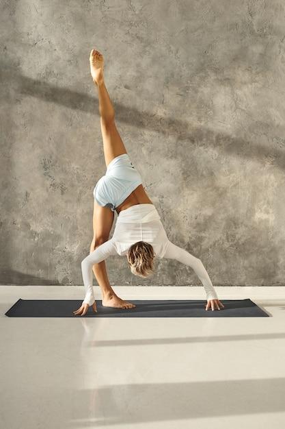 灰色の壁に対して立っているスプリットまたはurdhvaprasarita ekapadasanaのバリエーションを行っているジムで運動している日焼けした運動青年の垂直ショット。屋内で高度なヨガを練習しているスポーティな男に合う 無料写真