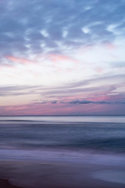 日の出中に海の上の美しいカラフルな空の垂直ショット 無料写真