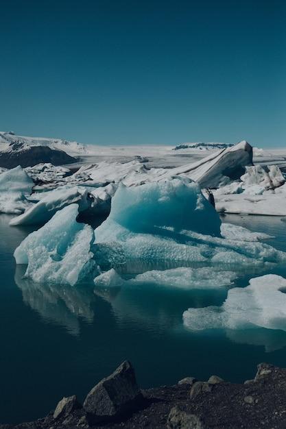 Вертикальный снимок красивых айсбергов на воде, снятых в исландии. Бесплатные Фотографии