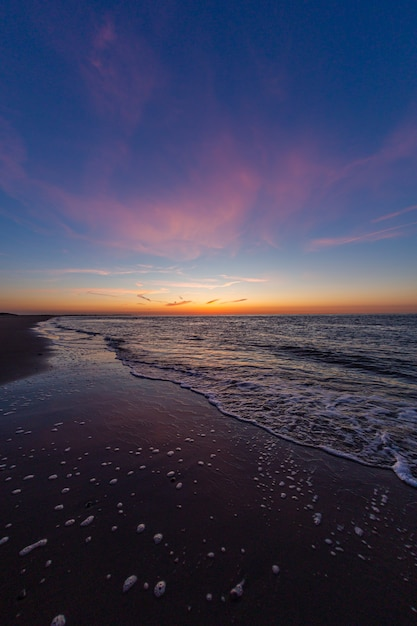 Вертикальная съемка спокойного океана во время захода солнца в vrouwenpolder, зеландия, нидерланды Бесплатные Фотографии