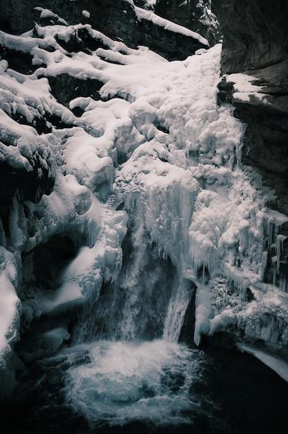 Вертикальный снимок замерзшего водопада в окружении скал зимой Бесплатные Фотографии