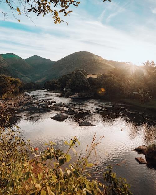 美しい川沿いの丘の垂直ショット 無料写真
