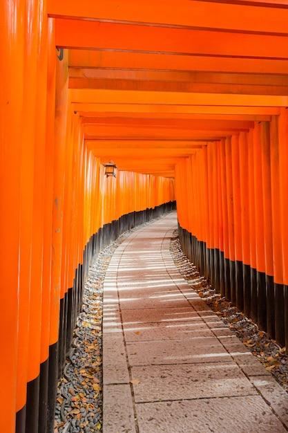 Вертикальный снимок оранжевого входа в храм фусими инари в киото, япония Бесплатные Фотографии