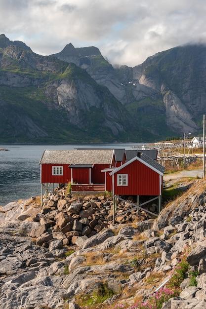 Вертикальный снимок красных коттеджей на береговой линии в хамнёй, лофотенские острова, норвегия Бесплатные Фотографии