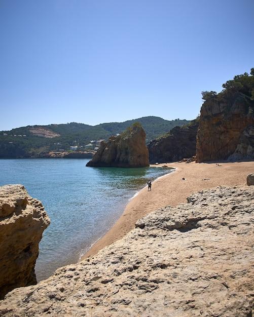 スペインのプラヤイラロハ公共ビーチで海の海岸の岩の垂直方向のショット 無料写真