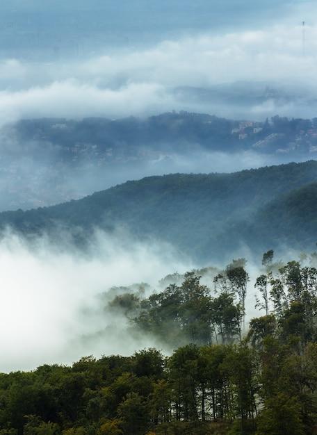 クロアチア、ザグレブのメドヴェドニツァ山を覆う煙の垂直ショット 無料写真