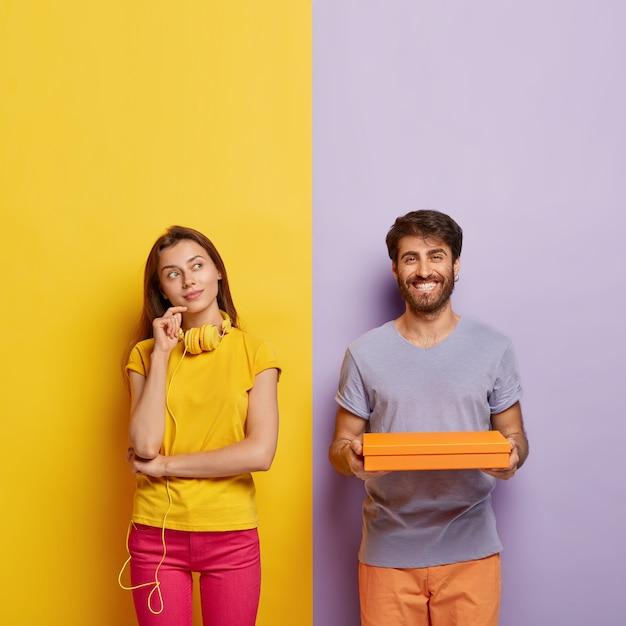 Вертикальный снимок задумчивой женщины, стоящей в задумчивой позе, обдумывающей что-то, в наушниках на шее, в желтой футболке и розовых штанах, веселый мужчина держит в руках картонную коробку Бесплатные Фотографии