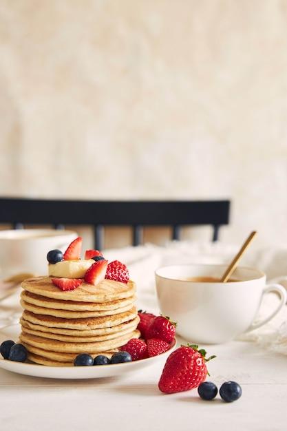 カラフルなフルーツとビーガンパンケーキの垂直ショットは、コーヒーとシロップです 無料写真