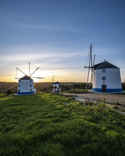 背景の澄んだ青い空に日の出の風車の垂直ショット 無料写真