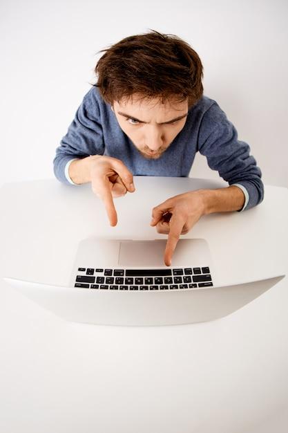 Вертикальный снимок молодого человека, офисный работник скучно поощрять себя работать, а не медлить, указывая на экран ноутбука Бесплатные Фотографии