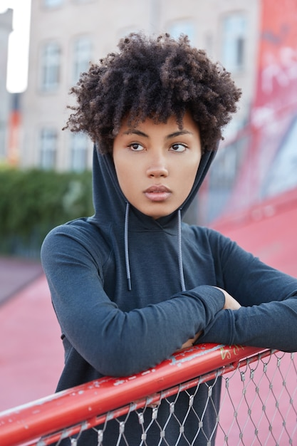 Vertical shot of pretty dark skinned woman with afro haircut, dressed in hood Free Photo