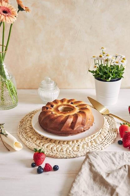 Colpo verticale di una torta ad anello con frutti su un tavolo bianco con sfondo bianco Foto Gratuite