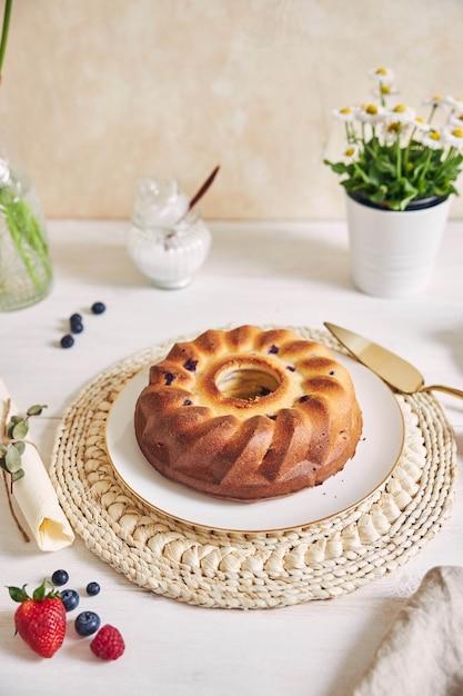 Colpo verticale di una torta ad anello con frutta su un tavolo bianco con superficie bianca Foto Gratuite