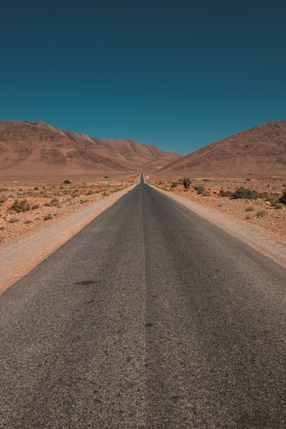 Vertical shot of a road in the middle of the desert and mountains captured in morocco Free Photo