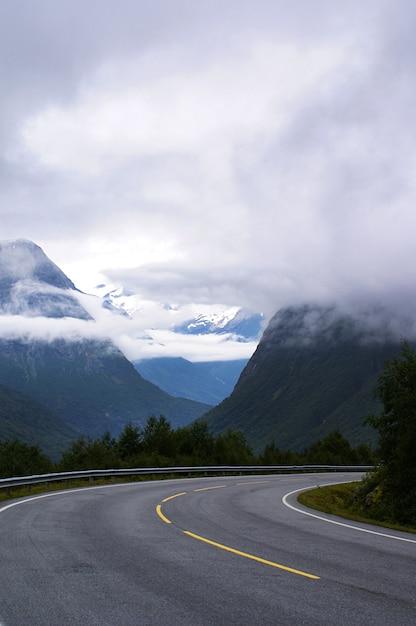 Colpo verticale di una strada circondata da alte montagne rocciose ricoperte di nuvole bianche Foto Gratuite